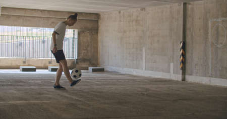 Teenager girl football soccer player doing ball tricks inside empty covered parking garage. Urban city lifestyle outdoors concepte. 4K UHD slow motion RAW graded footage Stockfoto