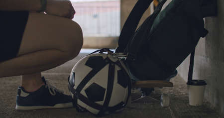 Teenager girl football soccer player takes ball out of the bag inside empty parking garage. Skater with skateboard. Urban city lifestyle outdoors concepte. 4K UHD slow motion RAW graded footage