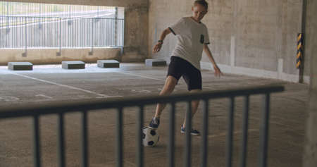 Teenager girl football soccer player doing ball tricks inside empty covered parking garage. Urban city lifestyle outdoors concepte. 4K UHD slow motion RAW graded footage Stock fotó