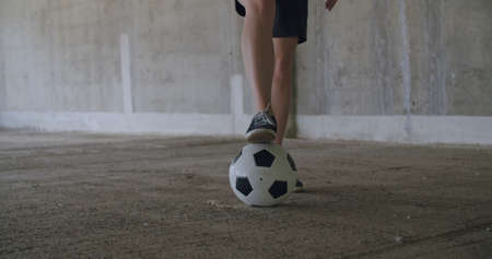 Teenager girl football soccer player practicing tricks, kicks and moves with ball inside empty covered parking garage. Urban city lifestyle outdoors concepte. 4K UHD slow motion RAW graded footage Stock fotó