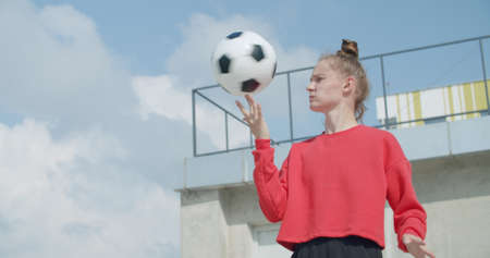 Teenager girl football soccer player doing ball tricks on rooftop empty parking garage. Urban city lifestyle outdoors concepte. 4K UHD slow motion RAW graded footage