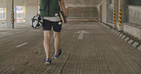Teenager girl football soccer player walking inside empty covered parking garage. Skater holding skateboard. Back view. Urban city lifestyle outdoors concepte. 4K UHD slow motion RAW graded footage Stockfoto