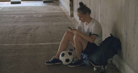 Urban girl using mobile phone. Caucasian teenager football soccer player sitting on skateboard texting on smartphone inside empty covered parking garage. 4K UHD slow motion RAW graded footage Stockfoto