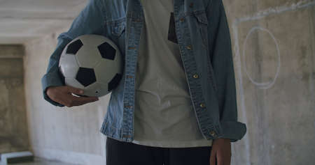 Teenager girl football soccer player holding ball inside empty covered parking garage. Urban city lifestyle outdoors concepte. 4K UHD slow motion RAW graded footage