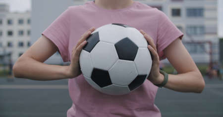 Young caucasian girl practicing soccer skills and tricks, holdind a soccer ball in her hands. Urban city lifestyle outdoors concept