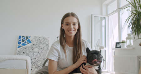 Smiling young woman blogger vlogger influencer sit at home with black french bulldog. Girl speaking looking at camera talking making video chat, conference call lifestyle blog vlog, webcam view