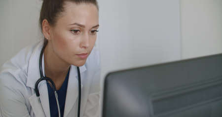 physician face looking at office monitor . Close-up of woman thinking about results, patients, work. Portrait of female looking laptop at home. Over display camera shot Stock fotó