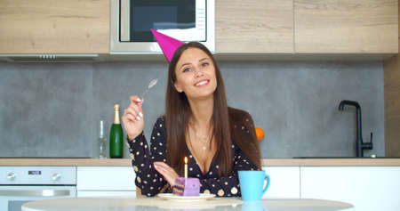 Young woman in party cap eating cake, having online birthday party with friends. Girl speaking looking at camera making video chat, lifestyle blog vlog, webcam view. Stay home, quarantine concept