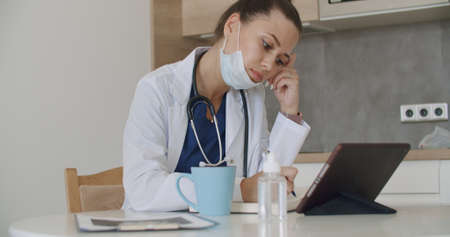 Lunch break in a medical facility. Side view of cute young doctor in white coat working at tablet answering an incoming call, on table next to cup with hot drink