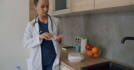 Lunch break in a medical facility. Female doctor in lab coat standing in clinic while kitchen in background Stock fotó