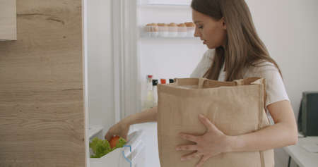 Cheerful young woman unpacking food bag into fridge. Pretty smiling housewife putting groceries in refrigerator Stock fotó