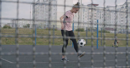Young caucasian girl practicing soccer skills and tricks with the football ball at sunset in an playground. Urban city lifestyle outdoors concept