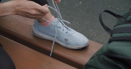 Closeup human hands tying laces on sneakers. Urban city lifestyle sport outdoors concept Stock fotó