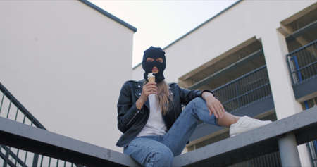 Stylish woman wearing black balaclava and leather jacket eats ice cream in wafle cone. Cocky girl sits on roof of city building provokes and looks at camera