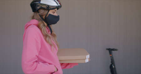 Delivery man waiting for customer at entrance door of modern house. Female courier wearing in protective medical mask holding boxes of pizza
