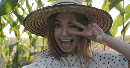 Close-up of happy young woman in a straw hat having fun with bundles of corn in her hands stands between the stems of plants with an agricultural field and takes a selfie on a smartphone