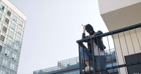 Stylish woman wearing black balaclava and leather jacket eats ice cream in wafle cone. Cocky girl stands on roof of city building provokes and looks at camera