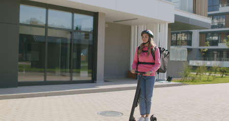 Young female deliveryman courier of takeaway rides on electric scooter with isothermal case box. Express fast food delivery service from cafes and restaurants