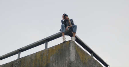 Stylish woman wearing black beanie and leather jacket. Cocky girl sits on roof of city building provokes and looks at camera 版權商用圖片