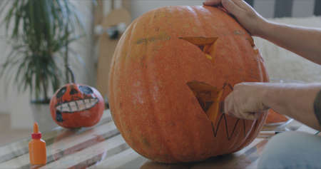 close-up of male hands carving out holes in a pumpkin for the holiday halloween