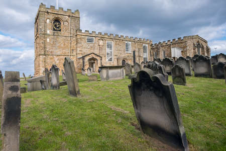 Caedmon memorial in Whitby, tombs in the foreground, overcast day, North Yorkshire, UK, England