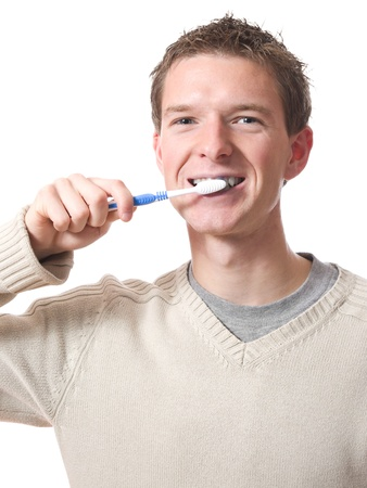 young smiling man brushing teeth with toothbrush isolated over white background photo