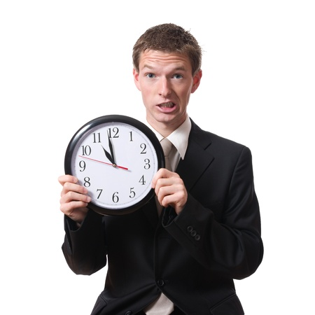 anguished: stressed businessman holding a clock isolated on white background Archivio Fotografico