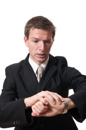 anguished: imprenditore tardivo, guardando il suo orologio isolato su sfondo bianco