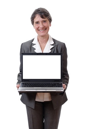 Smiling mature woman presenting laptop with empty screen isolated on white background photo