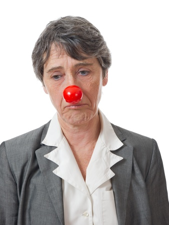 ridiculous: mature lady with red nose looking down on white background Stock Photo