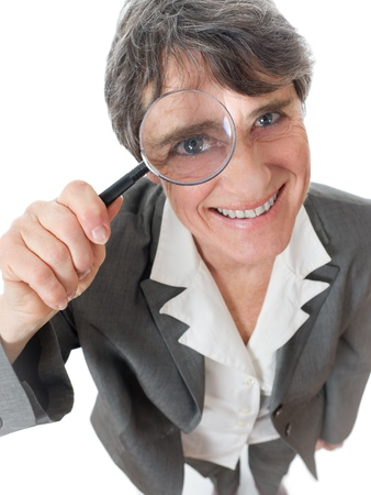 mature smiling lady looking through magnifying glass on white background photo