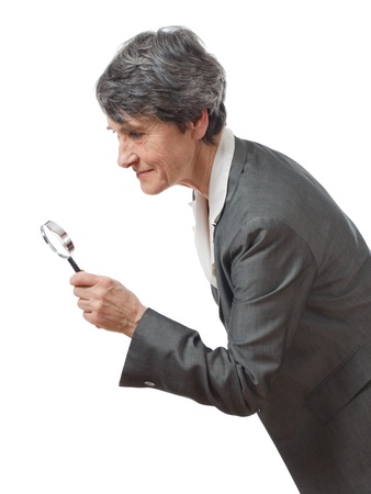 mature lady searching with magnifying glass on white background photo