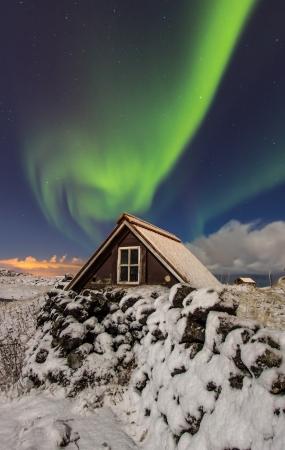 reykjavik: Luces del Norte por encima de antiguas casa de campo a las afueras de la ciudad de Reykjavik, Islandia