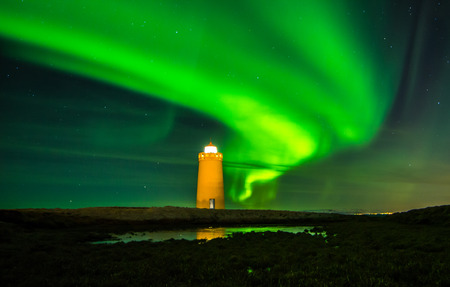 Northern lights dancing above a lighthouse in Iceland  Stock Photo