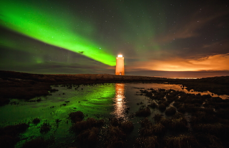 Lighthouse with northern lights above and reflections in a pond nearby  Stock Photo