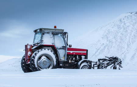 Old red tractor outside during winter time. photo