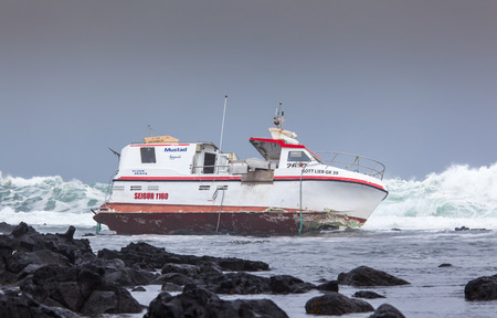 commercial fisheries: Grindavik, Iceland  May 14, 2015 : Commercial fishing boat  stranded at the rocky shore at the southwest part of Iceland.