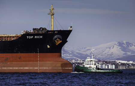 cargo vessel: Iceland - April 26, 2016 : Cargo vessel Top Rich with tugboat in Icelandic waters.