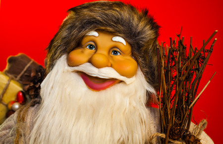 Portrait of a Santa Claus doll with red background.