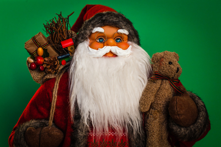 Portrait of a Santa Claus doll with green background.