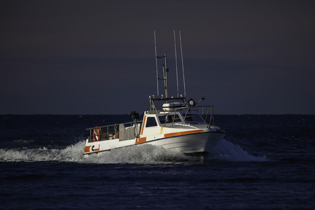 High speed commercial fishing boat sailing near coast of Iceland