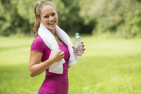 mladistvý: Cute sporty young woman drinking bottled water after training and working out in a park, standing smiling at the camera