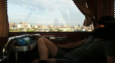 Traveler is sleeping on the bus ride, in the background the cityscape