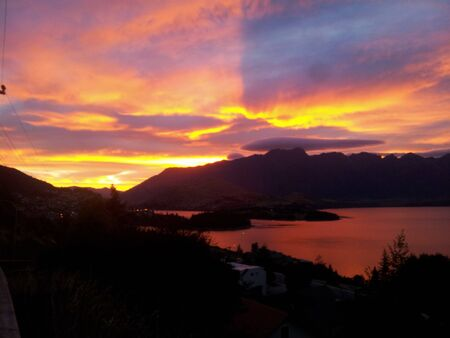 Morning in Queenstown, orange sky over the alpine mountains and the lake Wakatipu