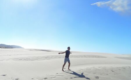 Man enjoying his freedom in the desert, sand flying in the air, blue sky Фото со стока