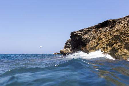 Sea wave splashing over the shore rocks with a high sea spray