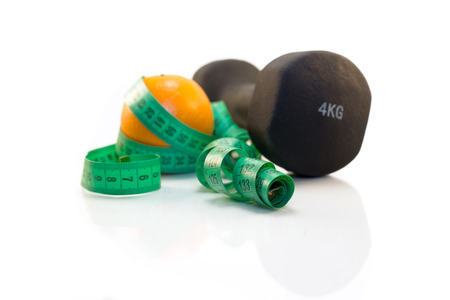 Dumbbell, orange and measuring tape on a white background. Isolated