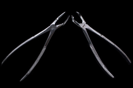 pincers: Dental pincers to remove the chewing teeth on black background.