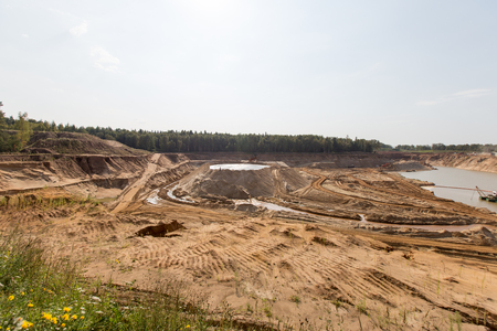 sand quarry: Extraction in a sand quarry with powerful machines and a washing lake. Stock Photo