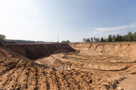 Extraction in a sand quarry with powerful machines and a washing lake. Stock Photo